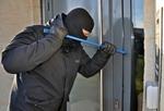 Ein Einrecher mit Sturmhaube versucht mit dem Kuhfuß eine Tür aufzuhebeln.