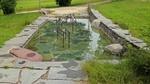 Ein Wasserbecken mit Haltegriffen in der mitte zum Wassertreten nach Kneipp.