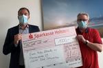 Dirk Burschberg, Leiter der Sparkasse-Holstein-Filiale in Bad Schwartau (links), und Bernd Lehmann, Gründer und Macher der Euro Kidz halten den symbolischen Scheck über 1.000 Euro.