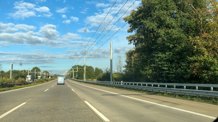 Autobahn mit LKW Stromtrasse