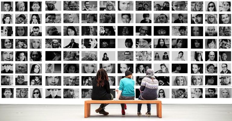 Drei Menschen sitzen auf einer Bank und betrachten eine Wand mit vielen Fotos von Menschen diverser Herkunft.