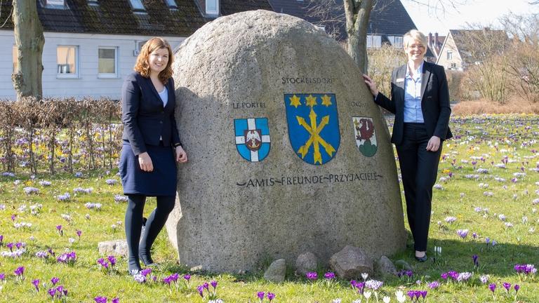 Bürgermeisterin Julia Samtleben, Christina Hinz (Sparkasse Holstein) am Stein der Städtepartnerschaften vor dem Herrenhaus
