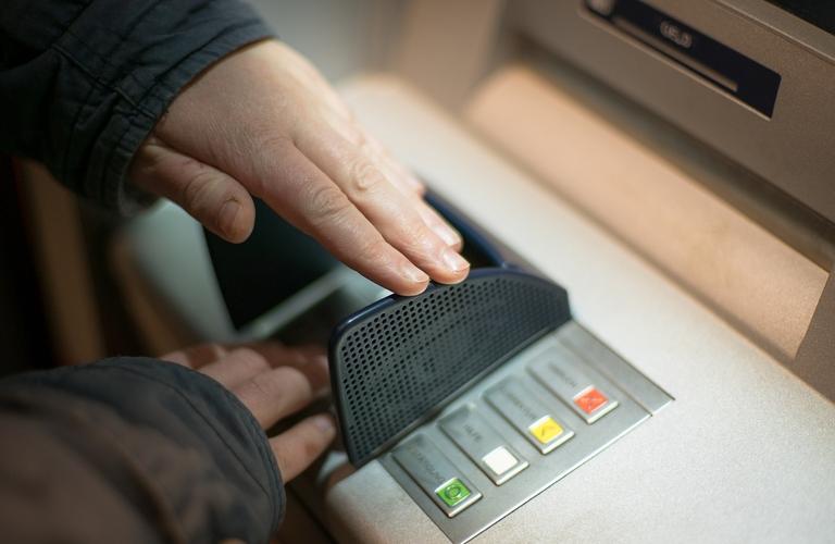 PIN-Eingabe mit abschirmender Hand am Geldautomaten