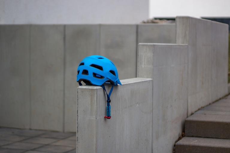Ein blauer Fahrradhelm liegt auf einer grauen Steinwand.
