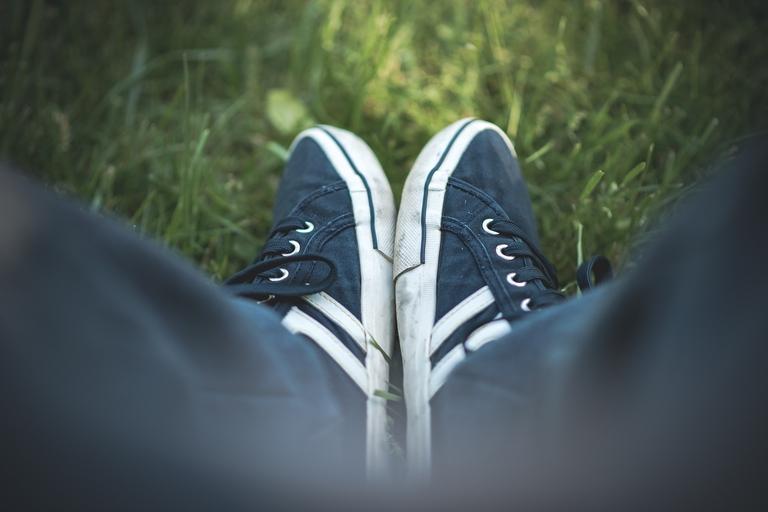 Sportschuhe auf Rasen von oben fotografiert