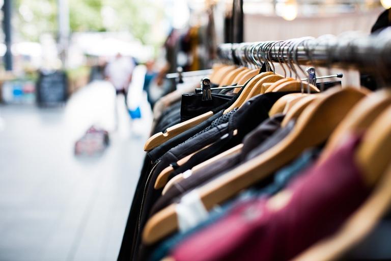 Kleidung auf Kleiderbügeln hängend an einem Kleiderständer.