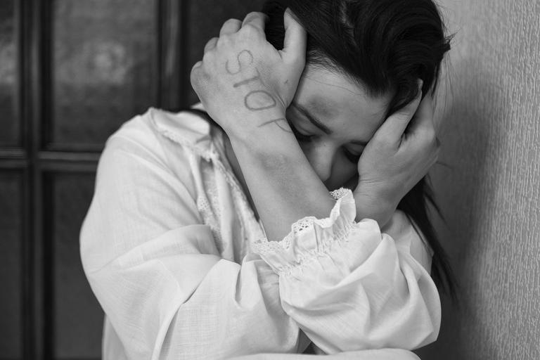 Eine Frau hält schützend die Arme um ihren Kopf, auf ihrem Handrücken steht STOP.