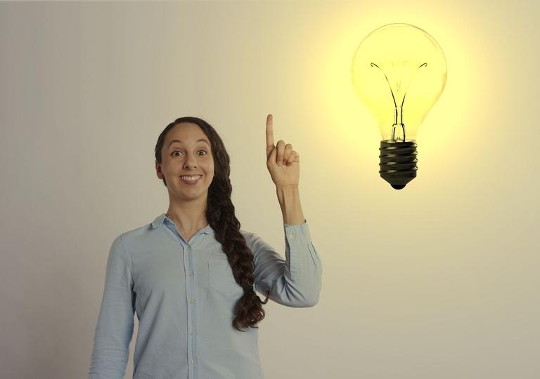Eine Frau, die den Zeigefinger hebt und eine helle Glühbirne symbolisieren eine Idee.