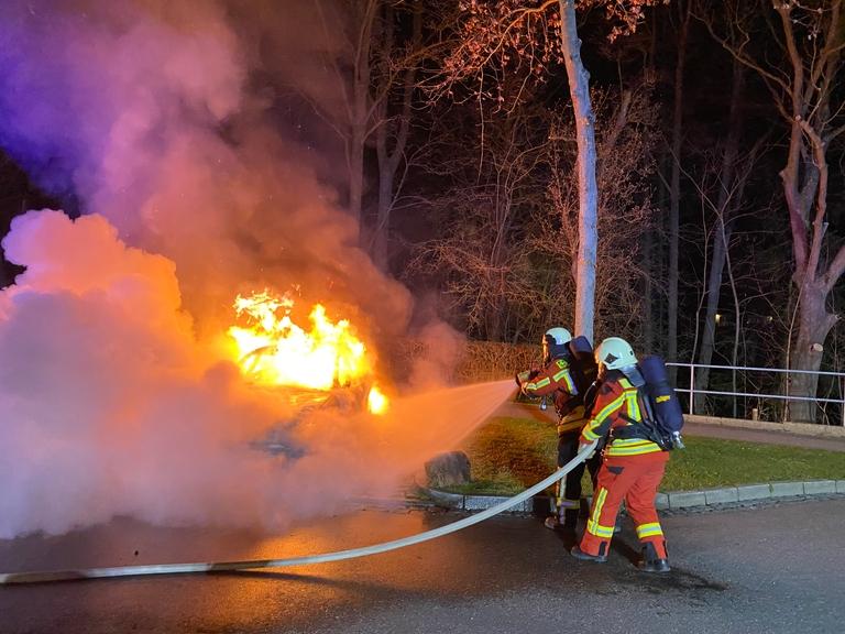 Zwei Feuerwehrleute löschen einen brennenden Pkw.
