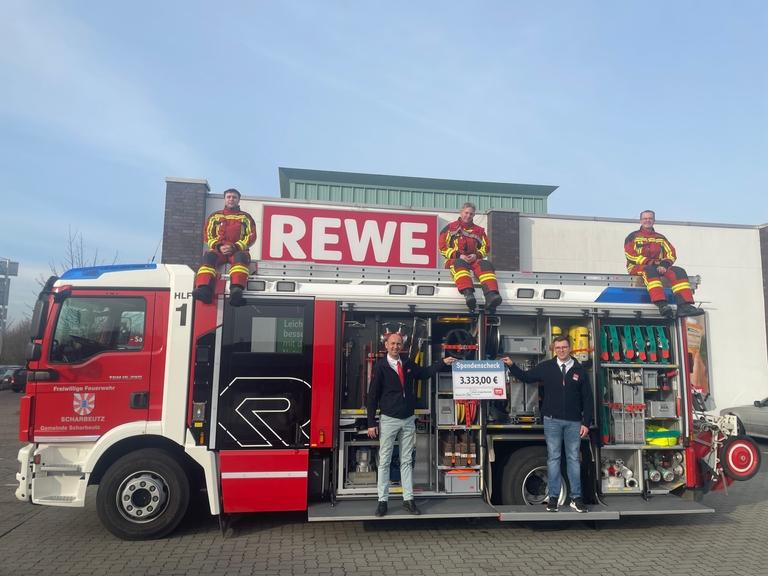 Drei Feuerwehrkameraden sitzen oben auf dem Löschfahrzeug, REWE Angestellte halten den Spendenscheck.