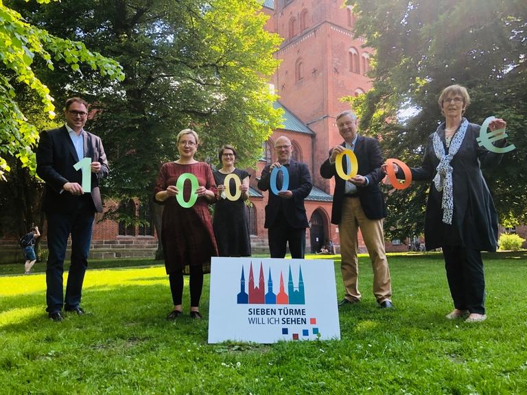 Bürgermeister Jan Lindenau, Petra Kallies, Margrit Wegner, Martin Klatt, Wolfgang Pötschke und Cornelia Schäfer symbolisieren die 100.000 Euro-Zuwendung mit Zahlen aus buntem Papier.