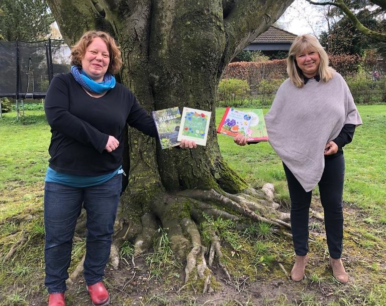 Leiterin der  Gemeindebücherei Stockelsdorf Kathrin Brümmer und Landtagsabgeordnete Sandra Redmann halten Gartenbücher.